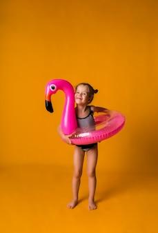 스트라이프 수영복에 쾌활한 금발 소녀는 플라밍고가있는 분홍색 풍선 원으로 약자이며 텍스트를위한 장소가있는 노란색 표면에 카메라를 찾습니다.