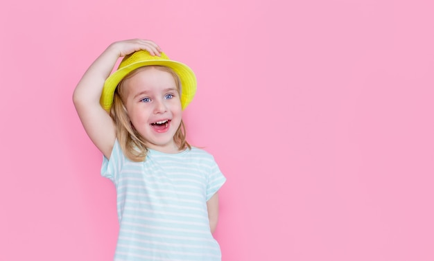 Cheerful little blonde girl in white blue striped t-shirt and yellow summer hat standing isolated over pink space and smiling, copyspace