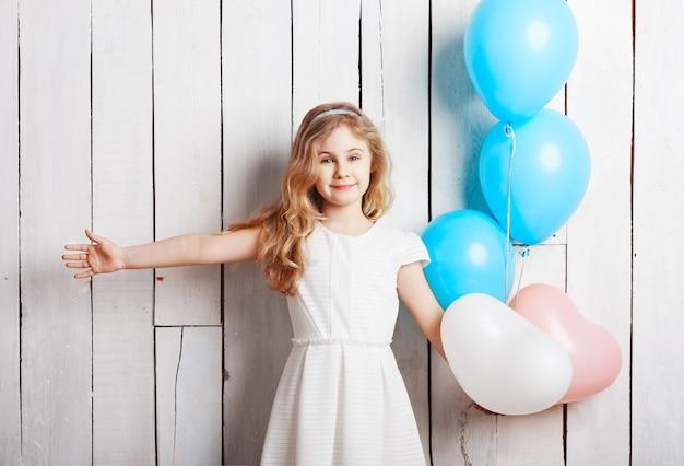 白い木の背景に風船と陽気な小さなブロンドの女の子。