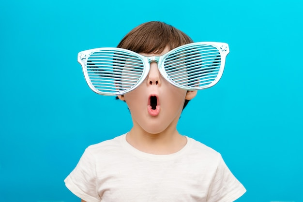Cheerful little boy in big glasses express a surprised face isolated on blue wall