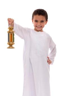 Cheerful little boy celebrating ramadan with lantern