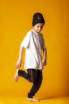Веселый мальчик, одетый в спортивные штаны и белую футболку, активно танцует, стоит на желтом фоне