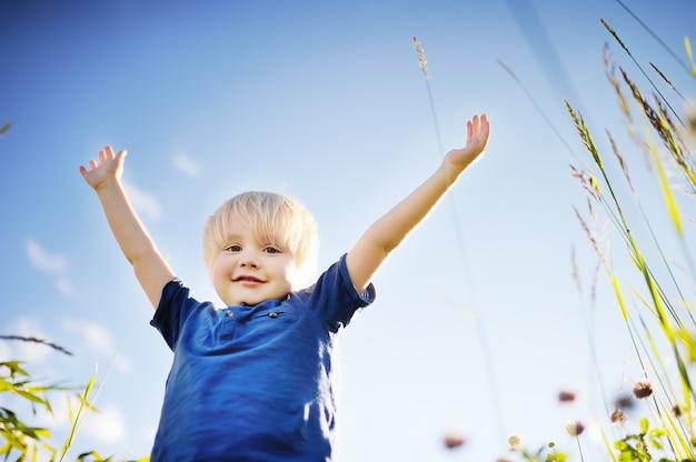 Cheerful little boy enjoying warm summer day