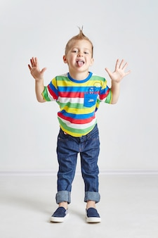 Cheerful little boy hamming and showing tongue