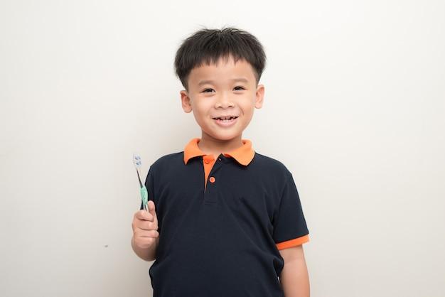 白い背景に歯ブラシを持った陽気な少年、分離された歯ブラシを持つ健康な混血少年のスタジオ ポートレート。
