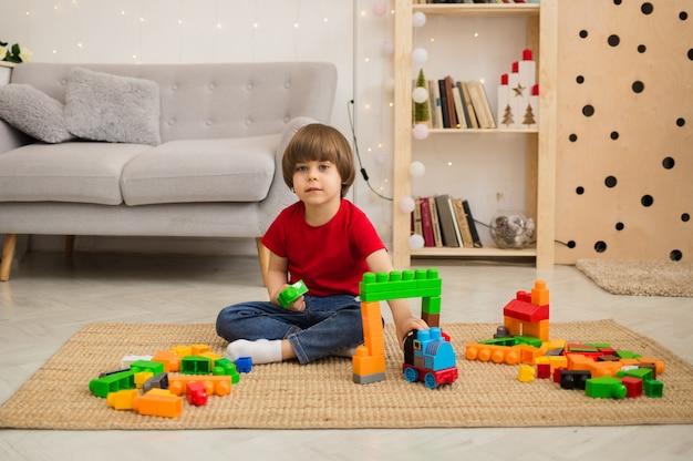 빨간 티셔츠와 청바지에 쾌활한 어린 소년은 소파 옆 바닥에 다채로운 건설 키트로 재생하고 정면을 봅니다.