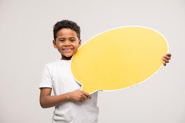 歯を見せる笑顔と白地に空白の黄色の吹き出しを示すアフリカ民族の陽気な男の子