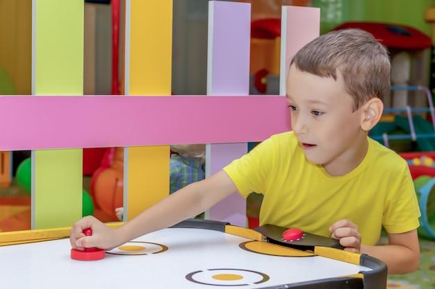 Веселый маленький мальчик играет в воздушный хоккей в аркадном центре