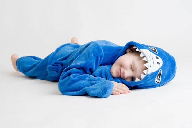 Cheerful little boy posing on white in pajamas, blue shark costume