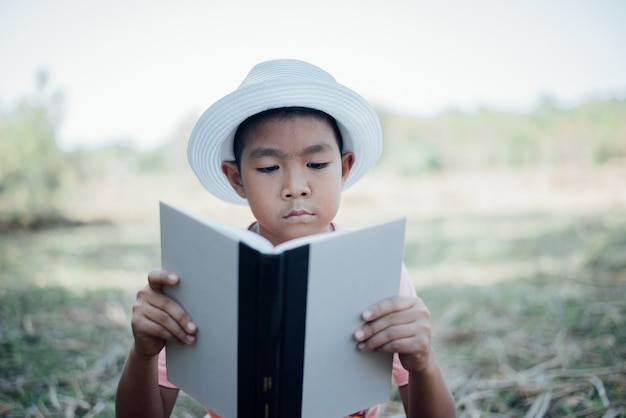 Cheerful little boy reading book