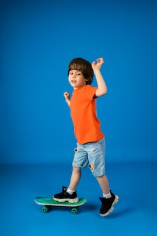 Cheerful little boy rides a skateboard on a blue surface with a place for text