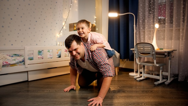 Cheerful little boy riding piggy back on his father at night. concept of child playing with parents and family having time together at night.
