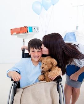 車椅子と彼の母親に座っている陽気な小さな男の子
