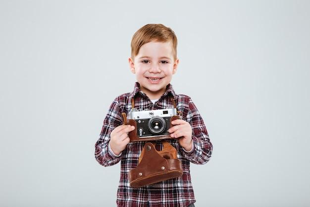흰 벽에 오래된 빈티지 사진 카메라를 들고 서 있는 쾌활한 소년