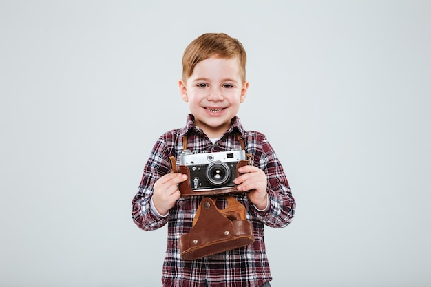 Cheerful little boy standing and holding old vintage photo camera over white wall