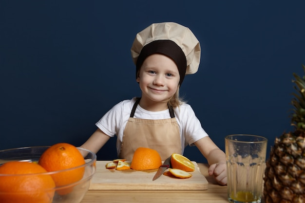 Cheerful little boy wearing apron and chef hat standing in modern kitchen, cooking fruit salad. portrait of cute caucasian male child in uniform making fresh juice, cutting and peeling oranges
