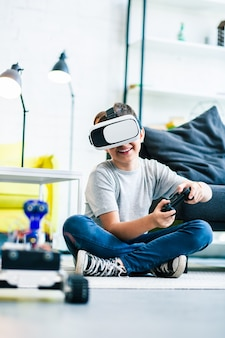 Cheerful little boy wearing vr glasses while testing his hand made robot