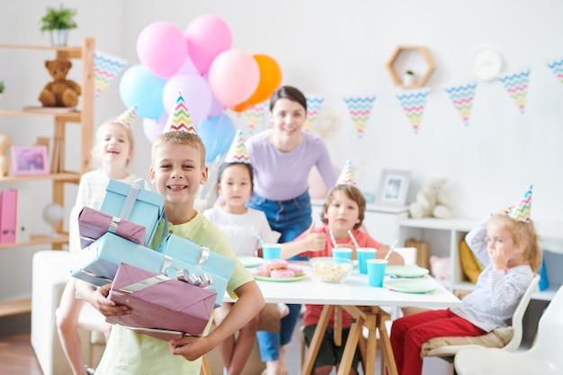Веселый маленький мальчик со стопкой подарочных коробок стоит, смеясь со своими друзьями и мамой