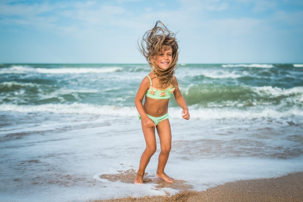 쾌활한 어린 백인 소녀 점프와 화창한 더운 여름 날에 모래 해안에 바다 파도에 재미