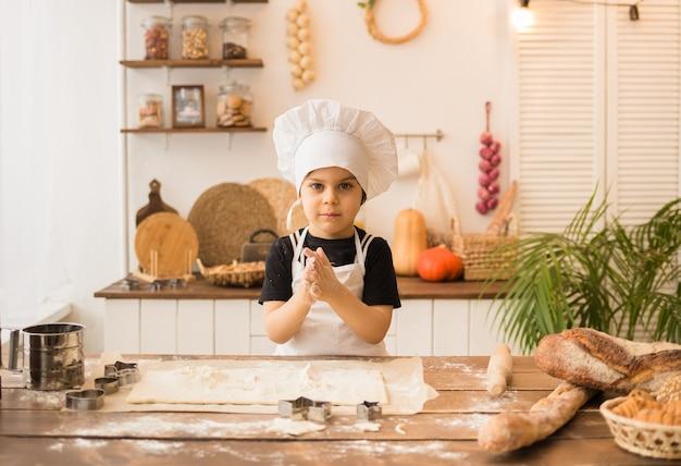 양복에 쾌활한 작은 요리사가 나무 테이블에 앉아 반죽으로 빵을 만듭니다.