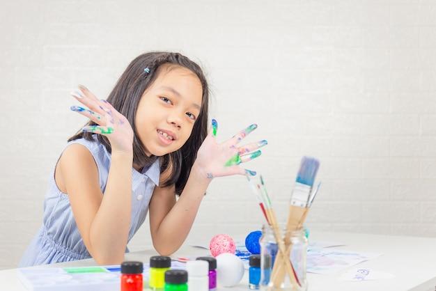 Веселая маленькая милая девочка играет и учится с раскрашиванием цветов