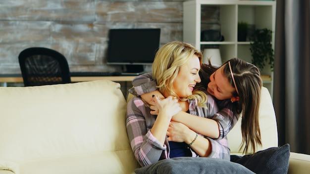 그녀의 어머니를 포옹 하는 쾌활 한 작은 딸. 엄마와 딸의 관계.