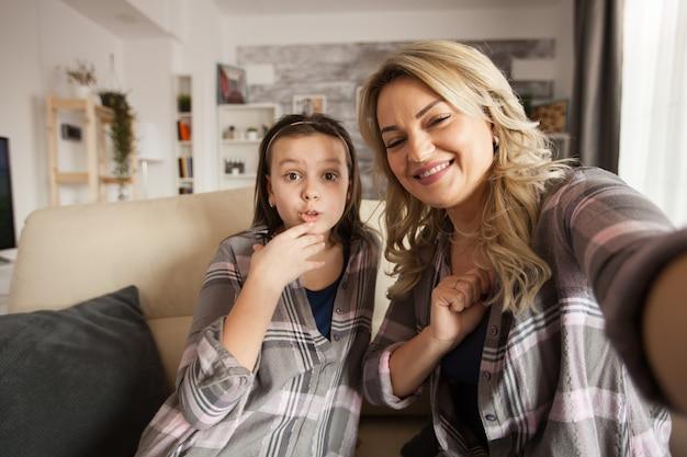 中かっこで陽気な小さな娘とカメラで肖像画を撮る若い母親。うれしそうな家族。