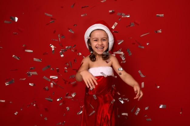 陽気な少女、サンタのカーニバルの衣装を着た愛らしい子供が喜ぶ、歯を見せる笑顔、コピースペースのある赤い背景の上に紙吹雪とスパンコールを投げます。新年とクリスマスのコンセプト