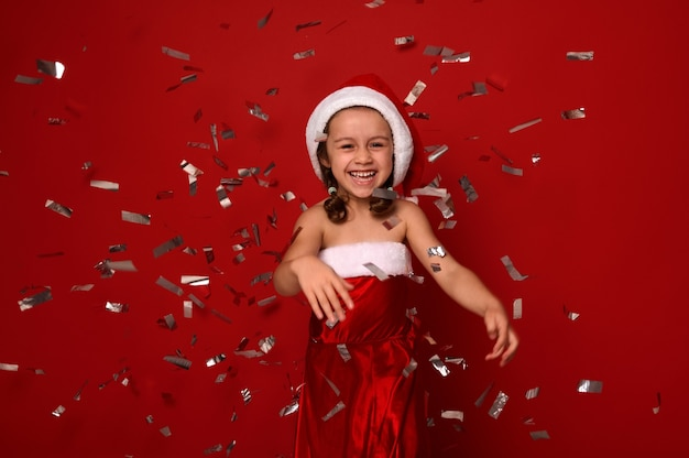 Cheerful little girl, adorable child dressed in santa carnival costume rejoices, smiles toothy smile , throwing confetti and sequins over red background with copy space. new year and christmas concept