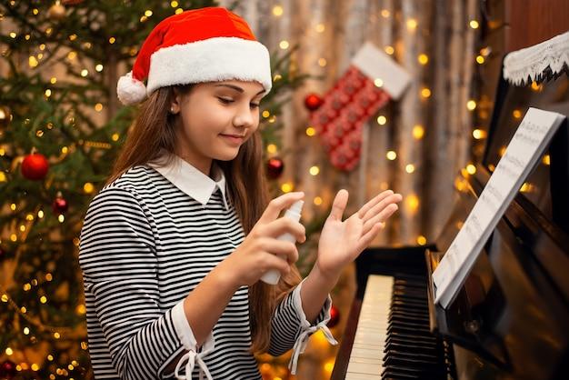 コビッドから身を守るために他の人の後にピアノを弾く前に手指消毒剤を適用する陽気な少女