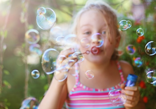 Cheerful little girl blows soap bubbles outdoor in summer