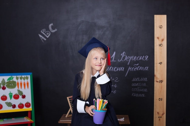 Cheerful little girl in cap of graduate master at school with pencils