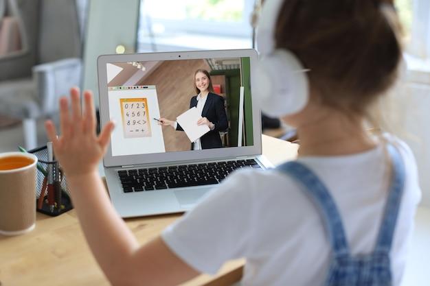 オンラインeラーニングシステムを介して勉強しているラップトップを使用してヘッドフォンで陽気な女の子の女の子