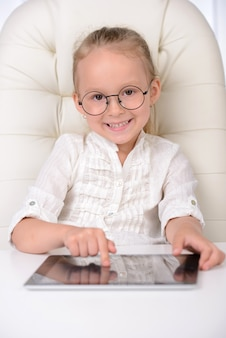 Cheerful little girl in glasses and formalwear.
