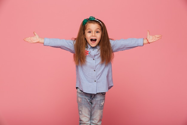 Cheerful little girl in hair hoop posing with open hands being friendly and welcoming