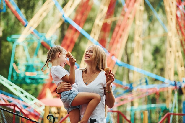 Cheerful little girl her mother have a good time in the park together near attractions