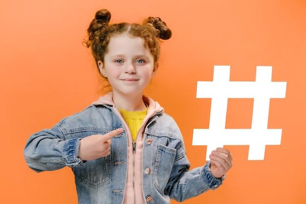Веселая маленькая девочка держит белый хэштег и указывает на него на оранжевом фоне