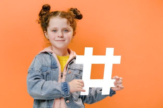 Веселая маленькая девочка держит белый хэштег на оранжевом фоне