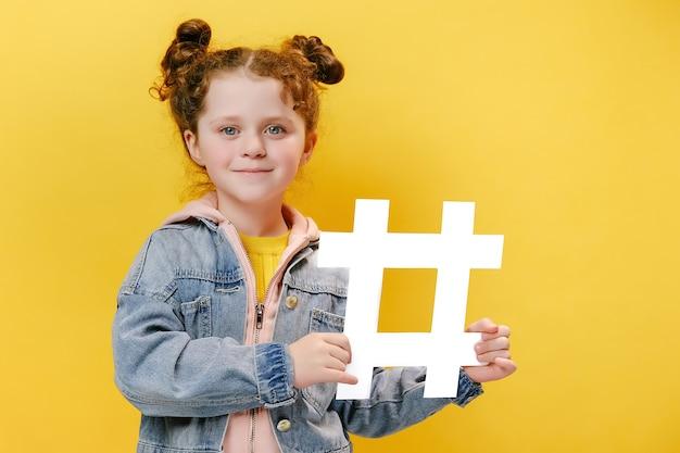 Веселая маленькая девочка держит белый хэштег на желтом фоне