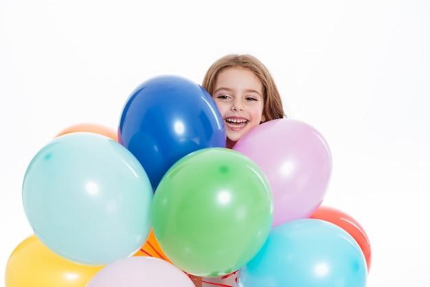 カラフルな風船を押しながら楽しい陽気な女の子