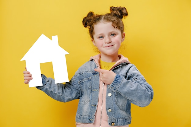 Cheerful little girl holding a white cardboard house and pointing at it on yellow background