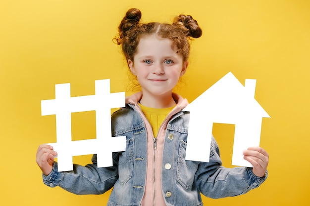 Cheerful little girl holding a white hashtag and house on yellow background