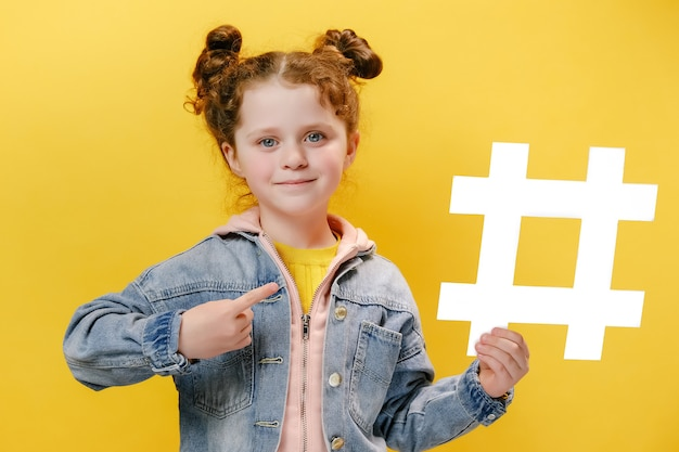 Cheerful little girl holding a white hashtag and pointing at it on yellow background