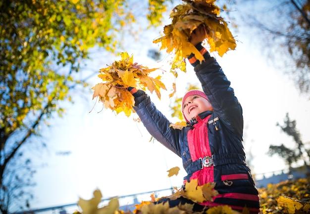 가을 햇살 가득한 공원을 걷는 동안 노란 단풍잎을 손에 들고 있는 쾌활한 소녀. 세 번째 가을 시즌 및 수확 개념