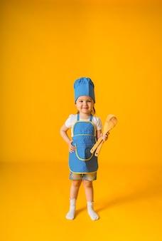 Веселая маленькая девочка в шляпе и фартуке шеф-повара стоит на желтой поверхности с местом для текста