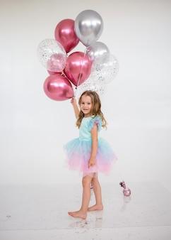 축제 드레스를 입은 쾌활한 어린 소녀는 텍스트를 위한 장소가 있는 흰색 배경에 풍선 다발을 들고 있습니다. 축제 배경