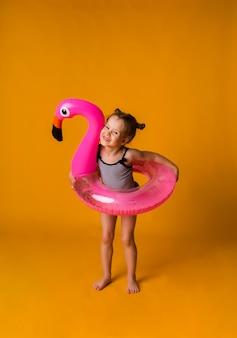 줄무늬 수영복과 플라밍고 모양의 풍선 수영 원이있는 명랑 소녀는 텍스트를위한 장소가있는 노란색 표면에 선다.