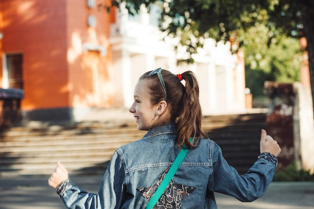 ぼやけた街の風景に対して彼女の背中に星とジーンズの服を着た陽気な少女。