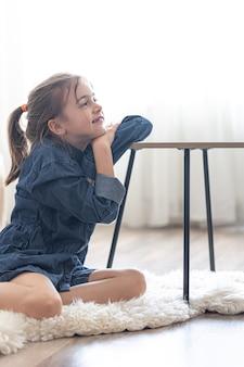 쾌활한 어린 소녀가 집에 있는 자신의 방에 있는 아늑한 양탄자에 있는 테이블에 앉아 있습니다.