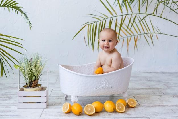 쾌활한 어린 소녀가 레몬을 넣은 아기 목욕에 앉아 텍스트를 위한 장소가 있는 흰색 배경에 있는 카메라를 보고 있습니다. 어린이를 위한 수처리